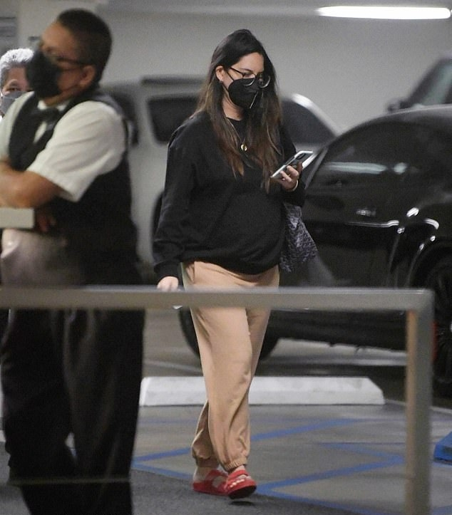 Olivia Munn wearing round red two-strap slippers by Birkenstock with buckle
