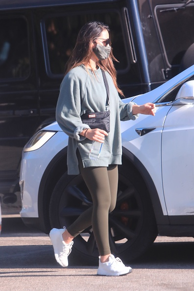 Olivia Munn donning a oversized blue grey sweatshirt with extra long sleeves and a V-neck