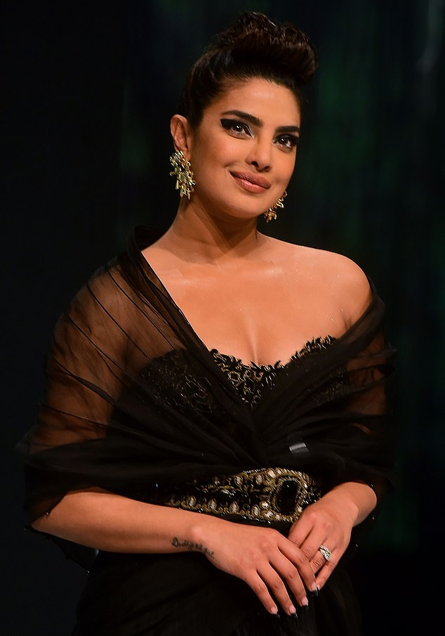Priyanka Chopra wearing a see-through black dress with a georgette material, pleated, a very low cut sweetheart neckline and cinched waist