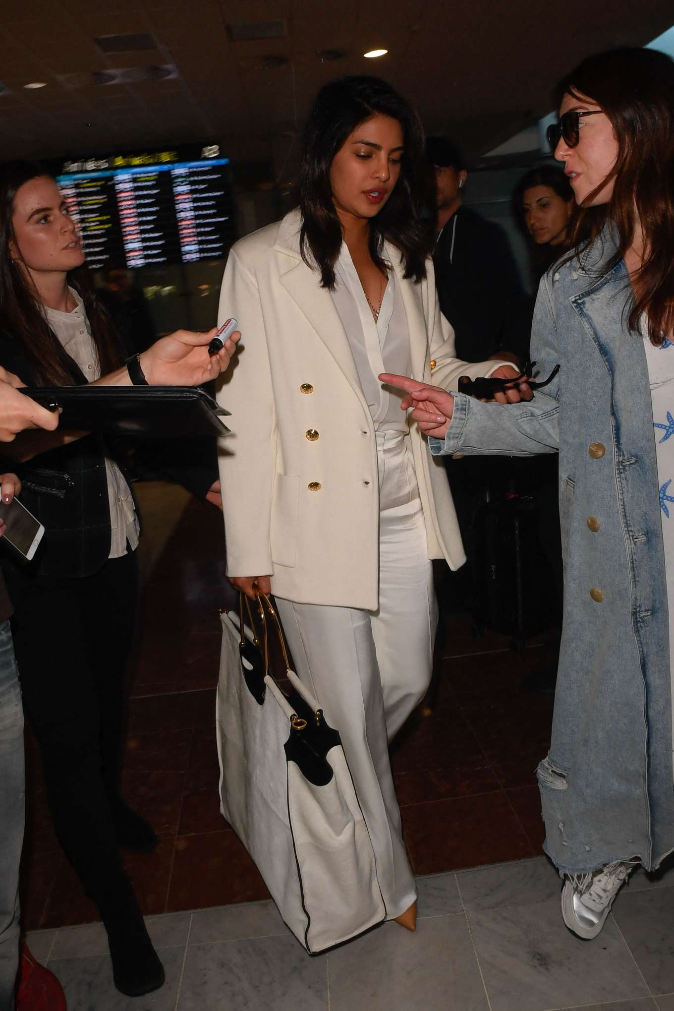 Priyanka Chopra, satin, white trousers, white double breasted blazer, tan pumps, high rise, wide leg. Priyanka Chopra wearing High rise shiny white satin trousers with a satin material