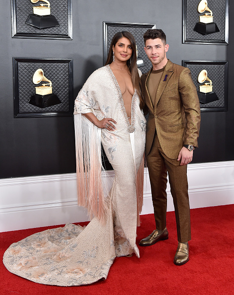 Priyanka Chopra wearing a Tassel white embroidered maxi gown with 3/4 sleeves, floral print, plunging neckline that almost went down to her waist and flared hem