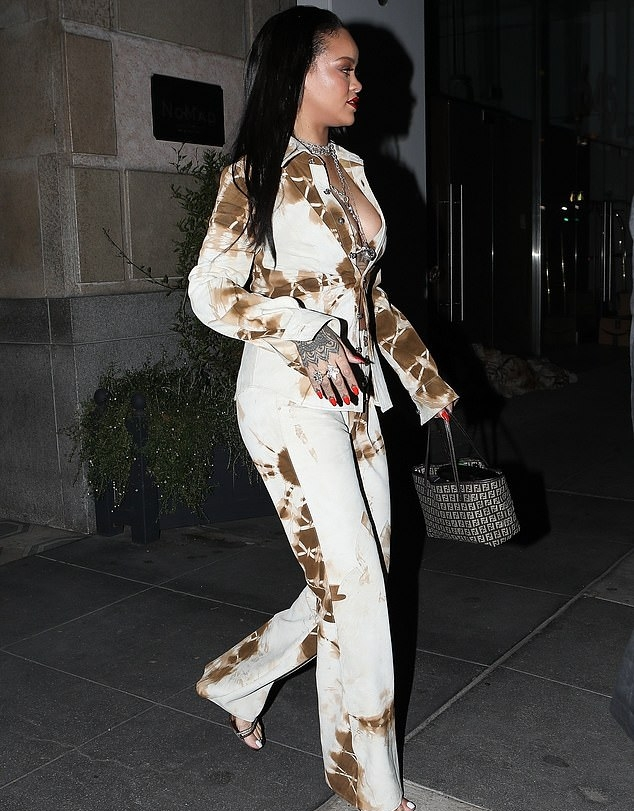 Rihanna donning strappy bronze sandals with high heel