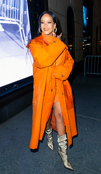 Rihanna donning pointy gold satin mid calf boots with high heel