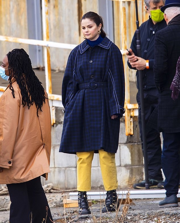 Selena Gomez donning a oversized navy blue button front woolen trench coat with full sleeves, spread collar and side pockets