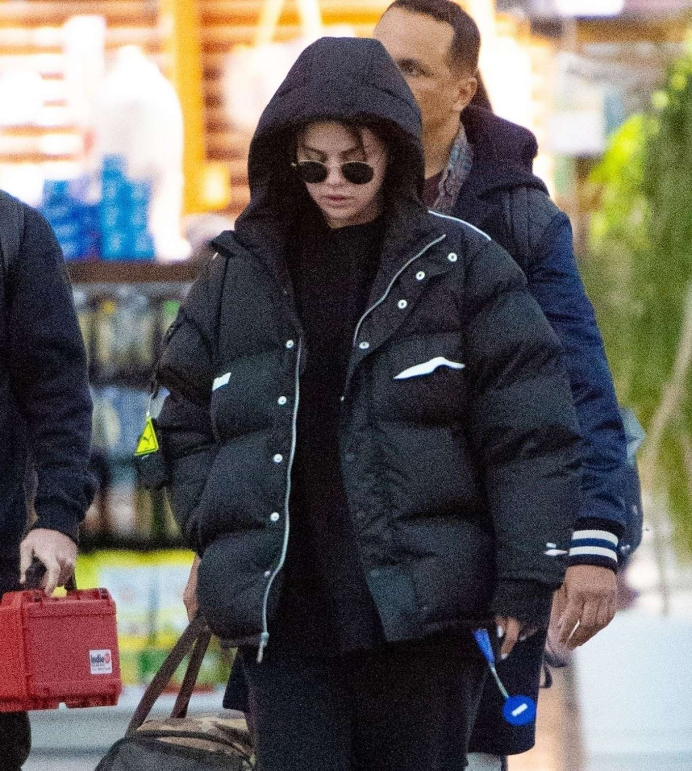 Selena Gomez donning a oversized black nylon puffer jacket with extra long sleeves and concealed button
