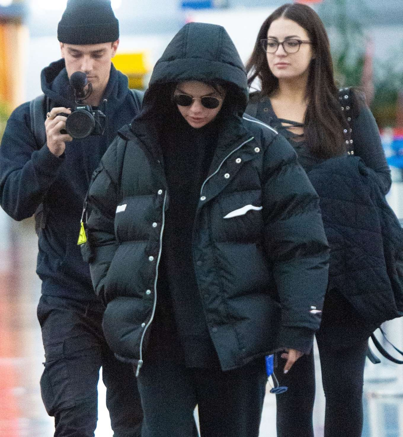 Selena Gomez, Puma jacket, black jacket, nylon, white Puma sneakers, black hoodie, hip length, extra long sleeves, front zip, oversized, black sunglasses, concealed button. Selena Gomez donning a oversized black nylon puffer jacket with extra long sleeves and concealed button