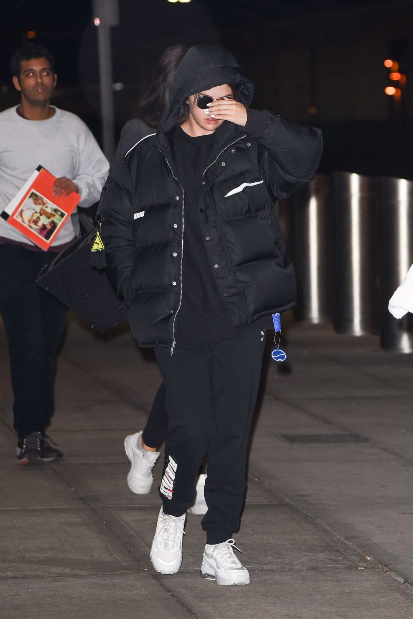Selena Gomez, Puma  jacket, black  jacket, nylon, black hoodie, white Puma sneakers, front zip, hip length, extra long sleeves, oversized, black sunglasses, concealed button