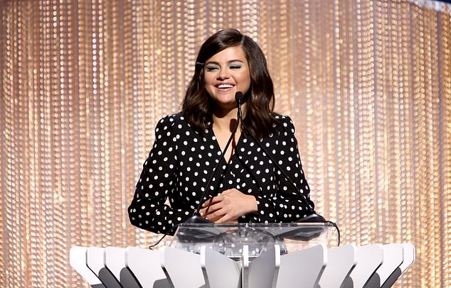 Selena Gomez rocking a black polka dot printed wrap dress with full sleeves, padded shoulder, a V-neck and cinched waist