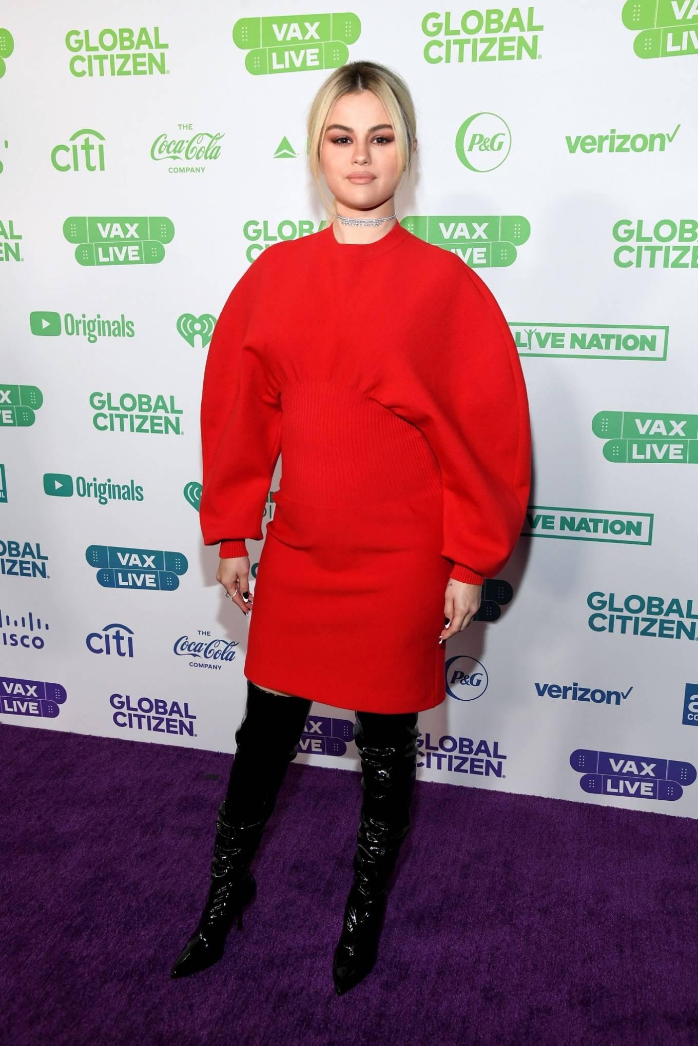 Selena Gomez, black boots, leather, red Bottega Veneta dress, ruched, pointed, thigh high, high heel, tapered toe. Selena Gomez donning ruched black leather thigh high boots with high heel