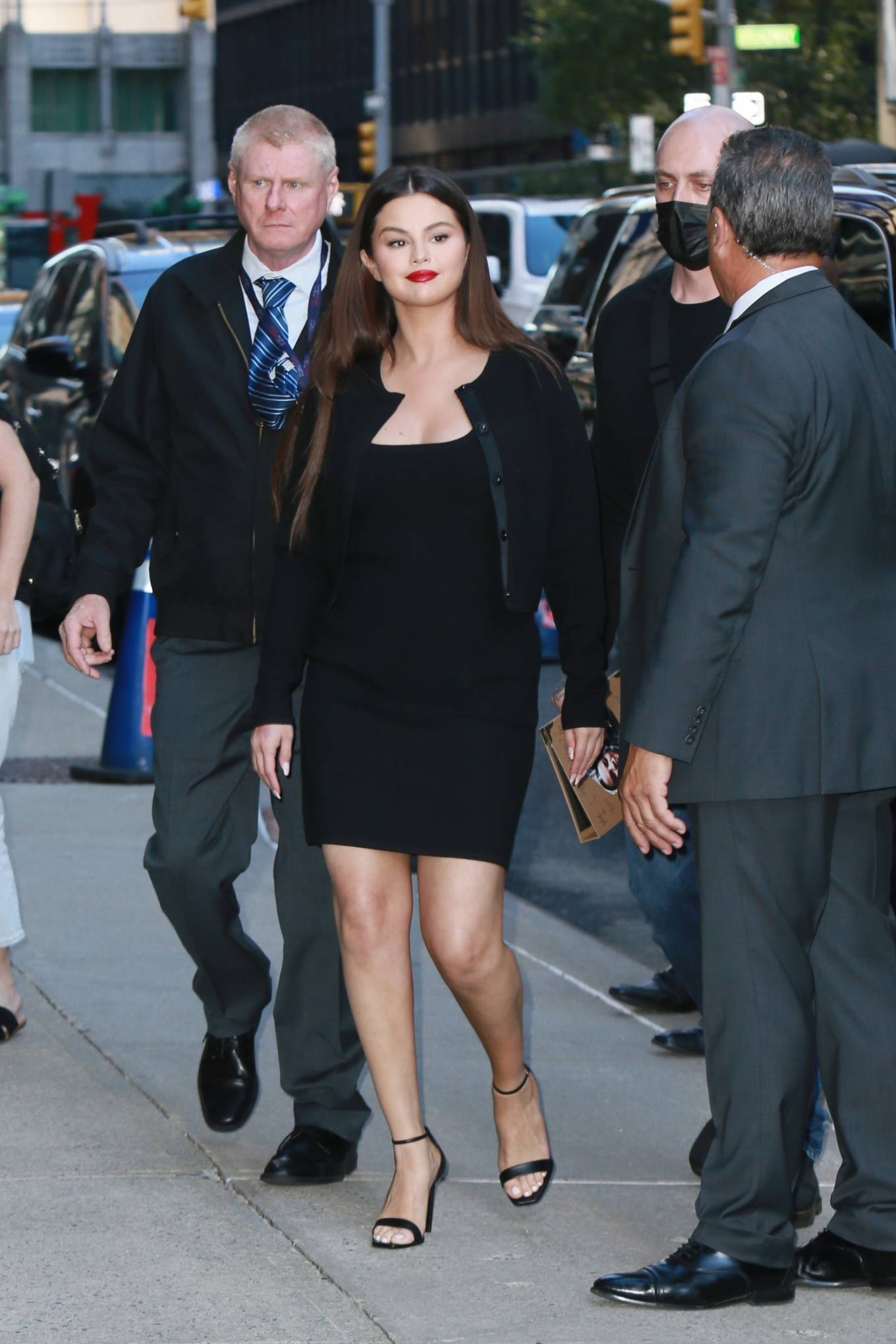 Selena Gomez wearing sleek black Saint Laurent ankle sandals with stiletto heels and ankle strap