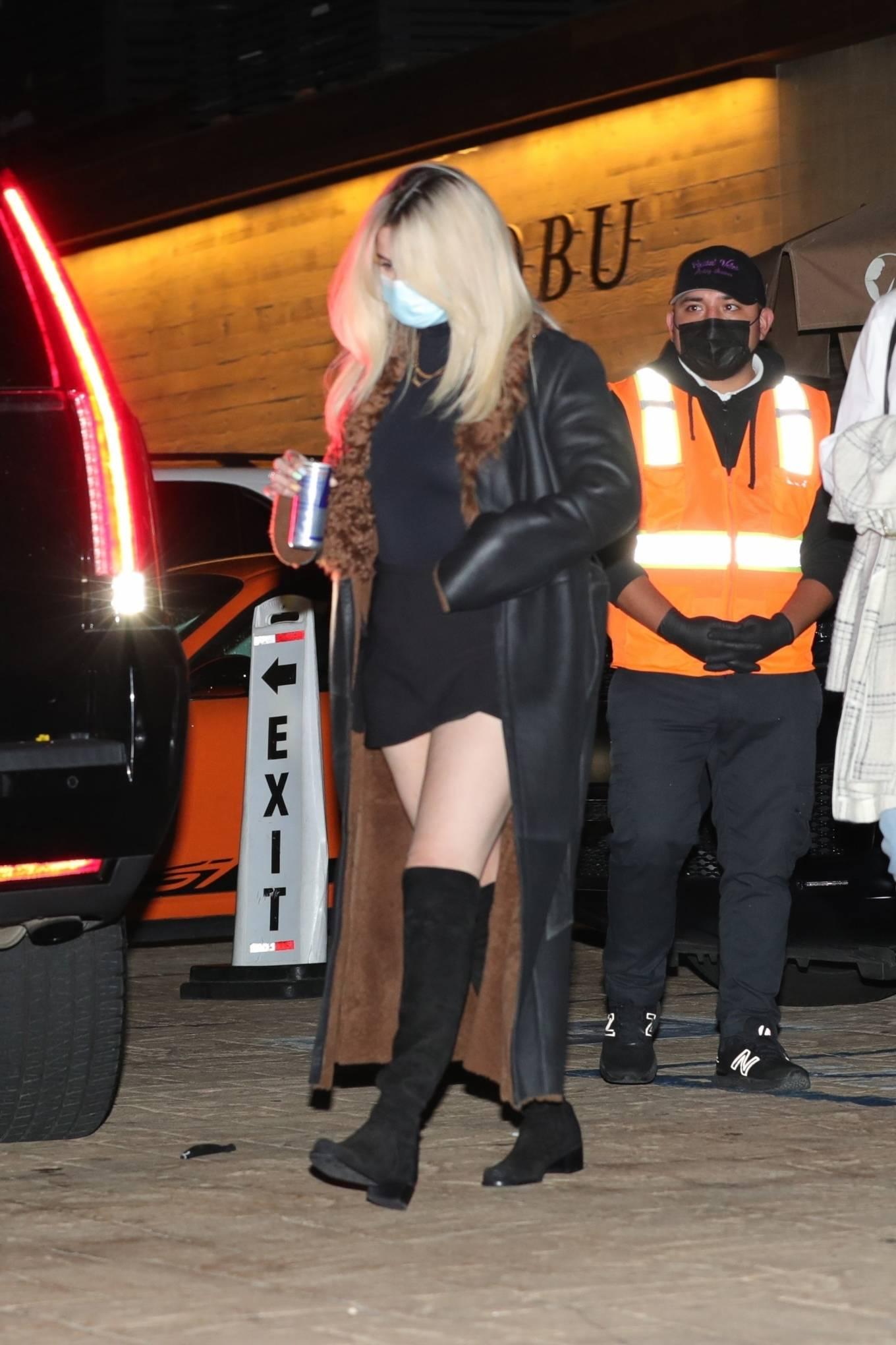 Selena Gomez rocking round black knee high boots with cuban heel