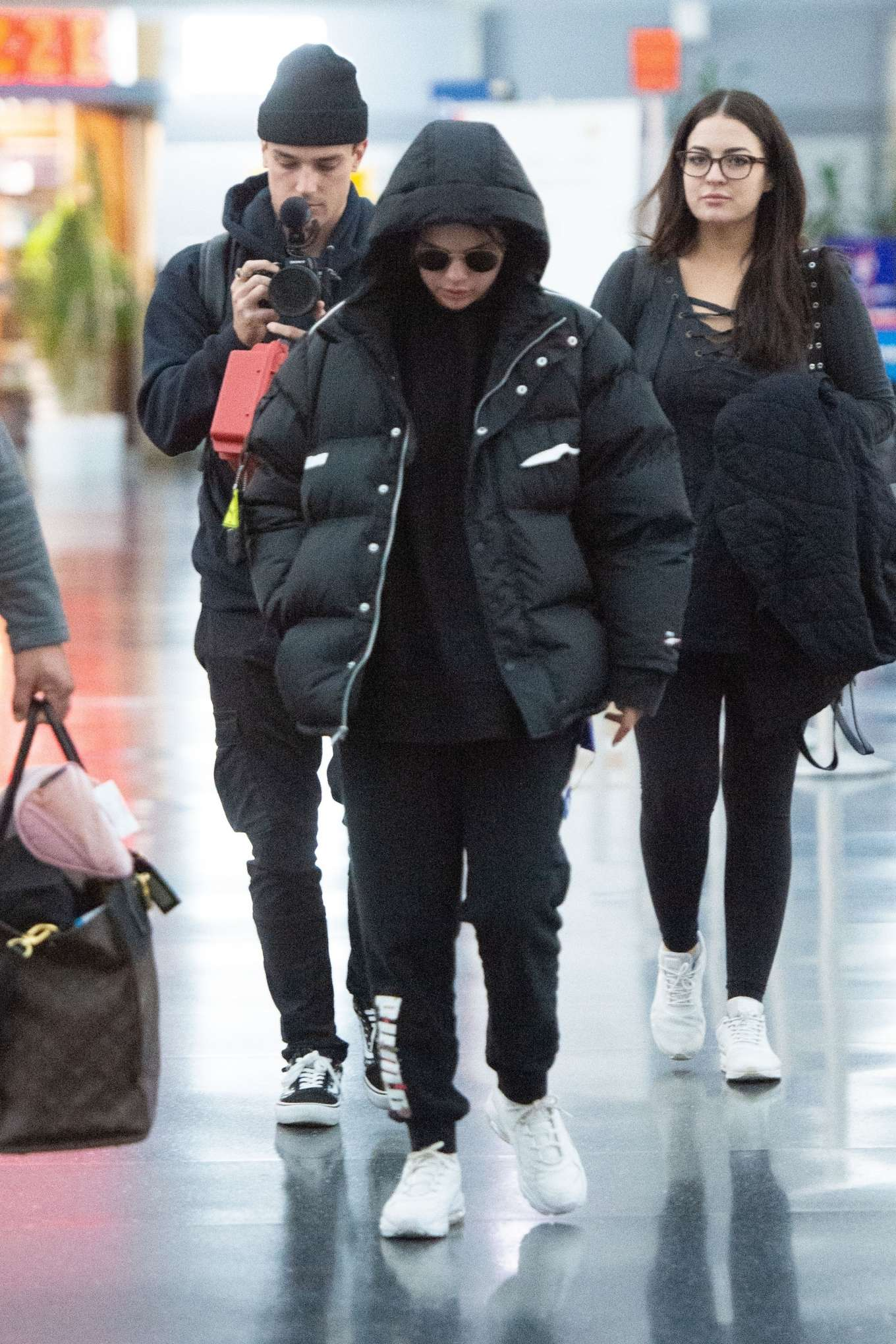 Selena Gomez, nylon, Puma  jacket, black  jacket, black hoodie, white Puma sneakers, hip length, extra long sleeves, front zip, oversized, black sunglasses, concealed button