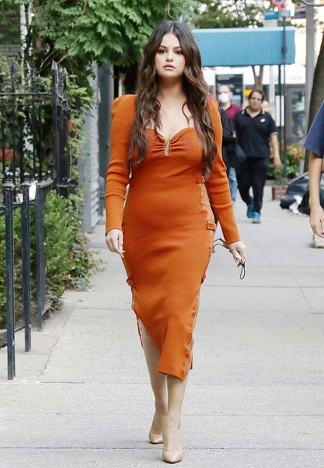 Selena Gomez wearing a figure hugging orange dress with a lace detailing fabric, full sleeves, puffed shoulder, sheer floral mesh panel detailing at sides and a sweetheart neckline