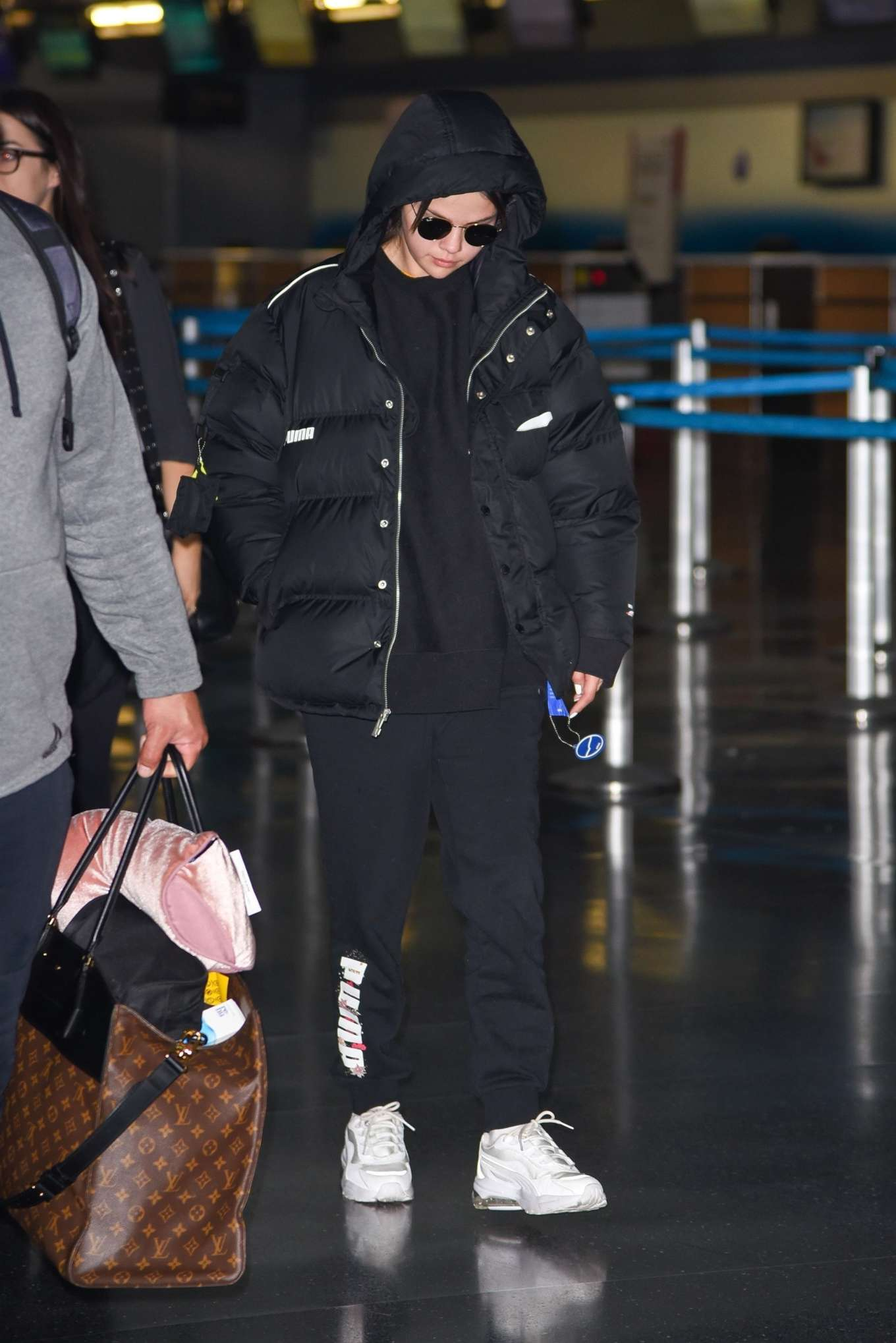 Selena Gomez, black  jacket, nylon, Puma  jacket, white Puma sneakers, black hoodie, front zip, hip length, extra long sleeves, oversized, black sunglasses, concealed button