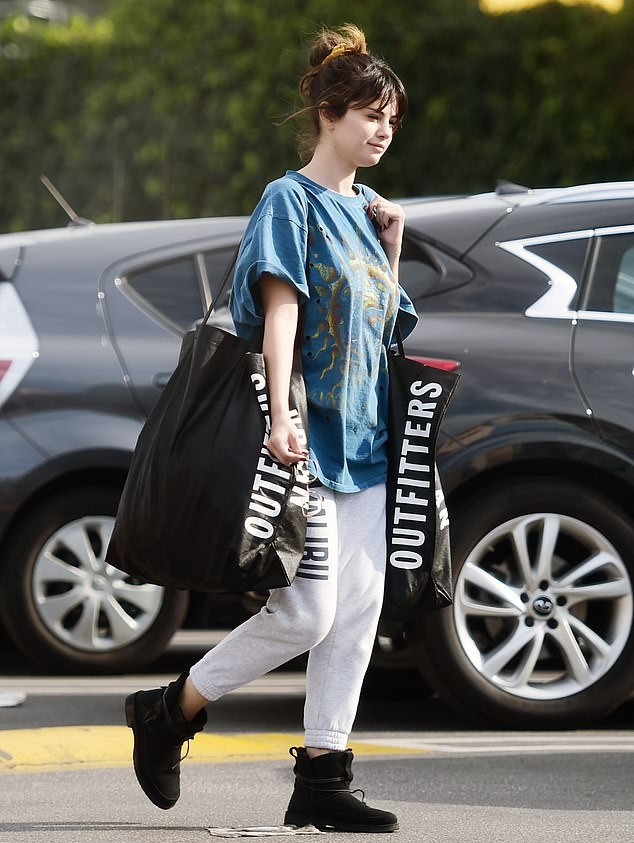 Selena Gomez rocking black leather ankle boots with square heel