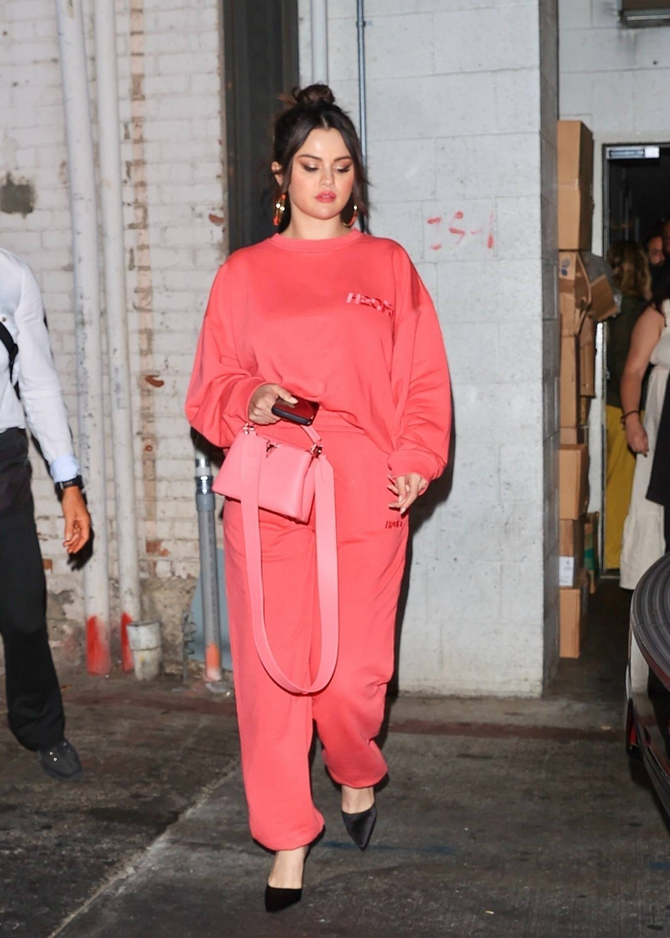 Selena Gomez rocking a oversized bright pink sweatshirt with a cotton material, full sleeves, brand logo and a crew neck