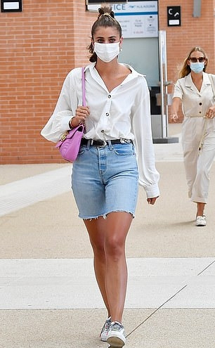 Taylor Hill donning white leather lace-up sneakers