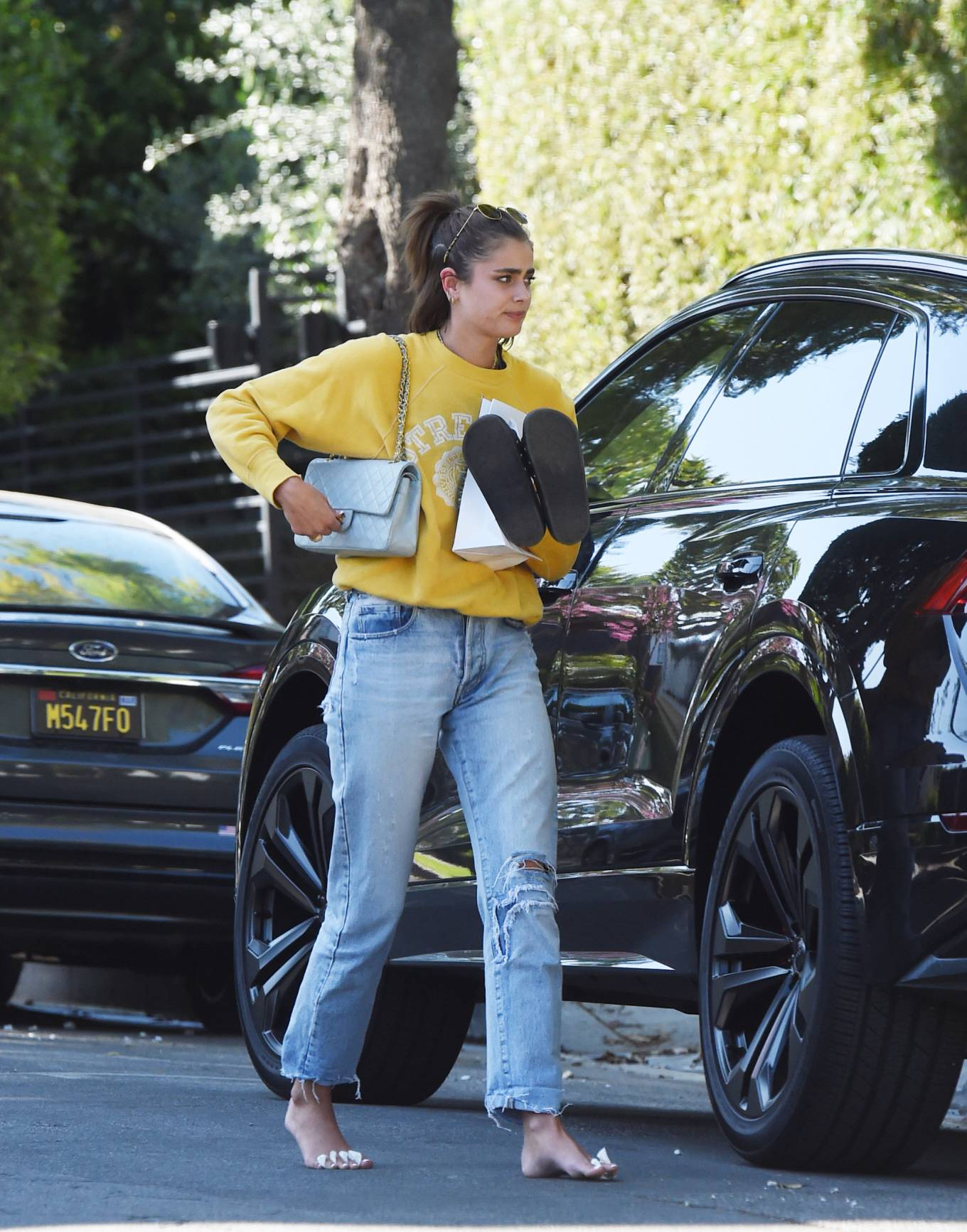 Taylor Hill wearing straight fit faded blue distressed jeans with busted hem with side pockets