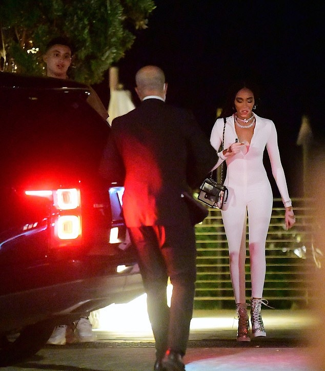 Winnie Harlow donning silver ankle boots with high heel
