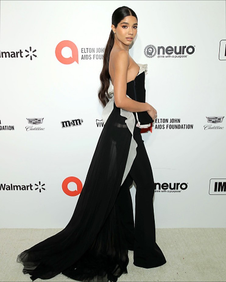 Yovanna Ventura rocking a black flowing bardot top with single sleeve, asymmetric design, a frilled neck and asymmetric hem